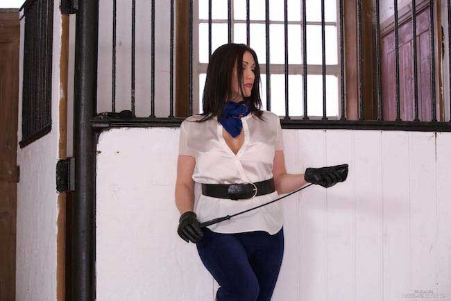 Gloves boots and cords Miss Hybrid in cleavage revealing blouse.